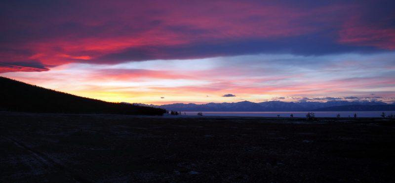 красивый розовый закат на озере и горах