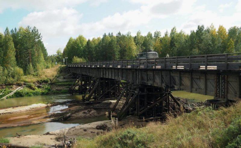 таёжный мост через реку из дерева